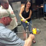 Couple participates in a glass blowing class for their anniversary